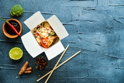 thai noodle in paper box with fried vegetables on gray concrete background. top view flat lay with copy space. street food to go