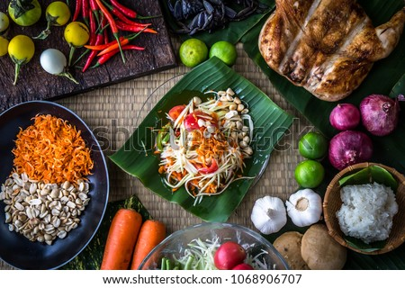"""Thai papaya salad or what we call """" Somtum """" in Thai with ingredients. The famous local Thai street food dish with the taste of hot and spicy. Food stylish photography concept"""