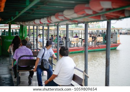 Thai people caption driving ferry boat across Chao Phraya River for send passengers to harbour at Nonthaburi city