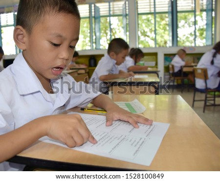 Thai primary students in elementary school are taking the final exam with intention and seriousness in classroom