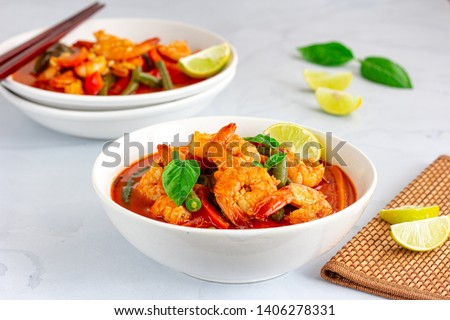 Thai Shrimp Red Curry in the Bowls with Chopsticks Served with Basil and Lemon on White Background. Thai Food, Oriental Food, Asian Food, Thai Cuisine Concept.