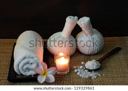 Thai spa massage setting with towel, frangipani, herbal compress balls and bath salt on spoon