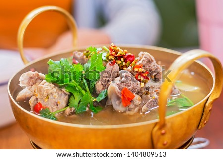"""Thai spicy pork bone soup, """"Leng tom zaap"""" is a clear pork bone soup filled with huge pork bones and dressed with chilies and herbs."""