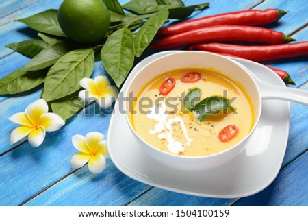 Thai spicy pumpkin and coconut milk soup with kaffir lime leaves , red chilli and galangal roots powder. Vegan, healthy food, gluten-free. Paleo- diet #1504100159