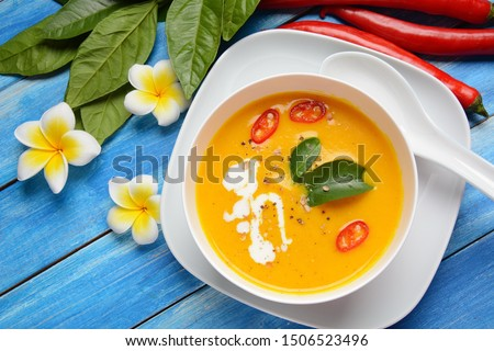 Thai spicy pumpkin and coconut milk soup with kaffir lime leaves , red chilli and galangal roots powder. Vegan, healthy food, gluten-free. Paleo- diet #1506523496