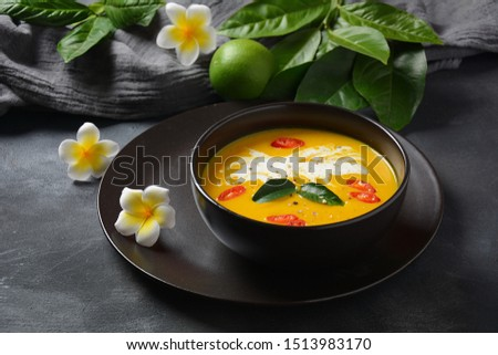 Thai spicy pumpkin and coconut milk soup with kaffir lime leaves , red chilli and galangal roots powder. Vegan, healthy food, gluten-free. Paleo- diet #1513983170