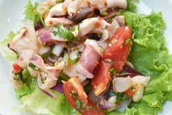 Thai spicy squid salad and fresh vegetable on plate