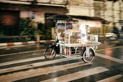 Thai street food vendor riding tricycle at rainy season at night in Phuket. High iso, motion blur and grain.