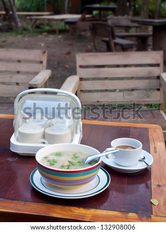 Thai style breakfast soft boiled rice mixed with ground pork, seasoning unit and coffee