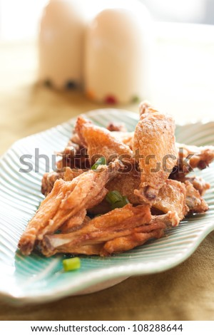 Thai style fried chicken wings on green table