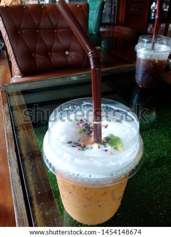 Thai tea with milk and whipped cream, sprinkle with a variety of sugar granules.