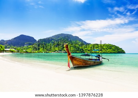 Thai traditional wooden longtail boat and beautiful sand beach at Koh Phi Phi island in Krabi province. Ao Nang, Thailand.