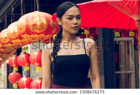 Thai Transgender model standing in front of Chinese red lanterns and a red umbrella outdoors
