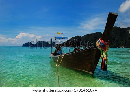 Thai typical boat, in Maya Bay, Phi Phi islands. Koh Phi Phi, Thailand. Turquoise sea. Long boat in tropical beach.