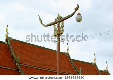 Thai Vintage Racing Boat Shaped Street Lamp against Temple's Tiled Roof and Cloudy Sky, Historic Place in Nan Province, Thailand
