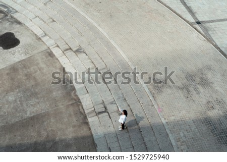 Thai woman who standing in a square raise her right hand up as a sunshade in the super hot summer. #1529725940