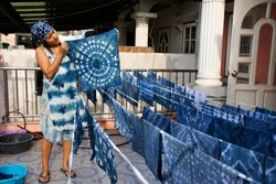 Thai women working Indigenous knowledge of thailand tie batik dyeing indigo color or mauhom color and hanging process dry fabric in the sun at outdoor on top of house in Nonthaburi, Thailand