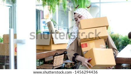 Thai young muslim online seller hold or carry many cardboard boxes packages to delivery or mail post to her customers. #1456294436
