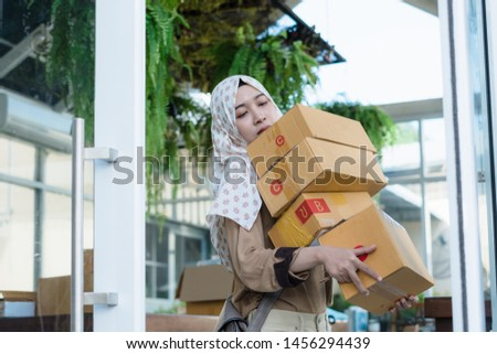 Thai young muslim online seller hold or carry many cardboard boxes packages to delivery or mail post to her customers. #1456294439