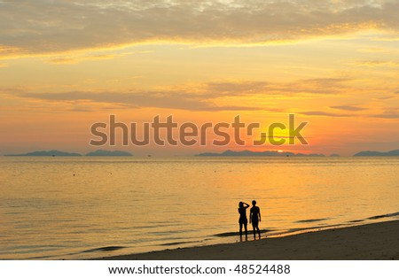Thailand. Andaman sea. Phi Phi island. Magic sunrise landscape and silhouettes of two girls making photos