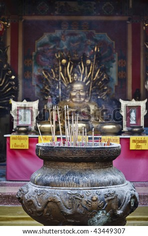 Thailand, Bangkok, Chinatown, Buddhist temple, burning incenses offered to a golden Buddha statue