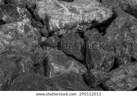 Thailand / June 2015. Black and White Rocks background. The rocks was scattered along the shore line to prevent land erosion and it creates nice pattern.