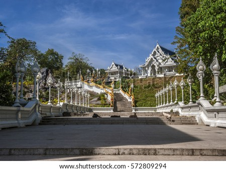 Thailand, Krabi, Krabi town. Temple Wat Kaew Korawaram - white facade and dark blue roof. Railing stairs leading to the temple, in the form of long, beautiful dragons Nagi.