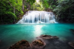 Thailand outdoor photography of waterfall in rain jungle forest. Trees, foliage and clear water of mountain river