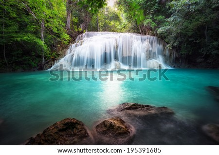 Thailand outdoor photography of waterfall in rain jungle forest. Trees, foliage and clear water of mountain river  #195391685