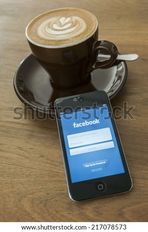 THAILAND - SEPTEMBER 05, 2014: Facebook application login screen on ipod apple product with morning coffee and wood desk background.