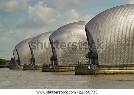 Thames Barrier on a sunny day with blue sky and fluffy white clouds