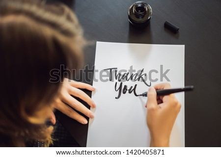 Thank you. Calligrapher Young Woman writes phrase on white paper. Inscribing ornamental decorated letters. Calligraphy, graphic design, lettering, handwriting, creation concept