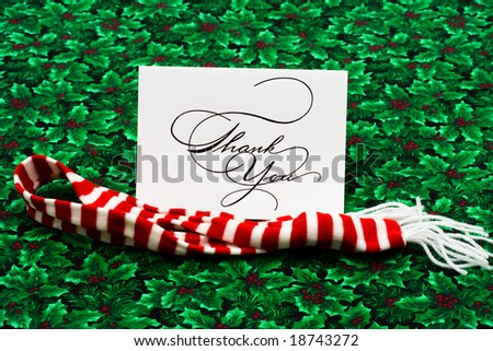 Thank you card and striped scarf on leaf and holly berry background, thank you card