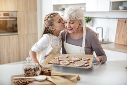 Thank you, granny. Cute girl is kissing cheek of her grandmother with love. Senior woman is holding pray with self-baked cookies and smiling