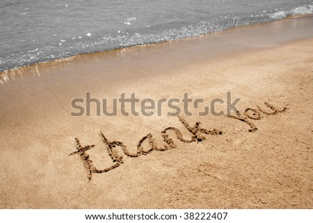 Thank you handwritten in sand on a beach