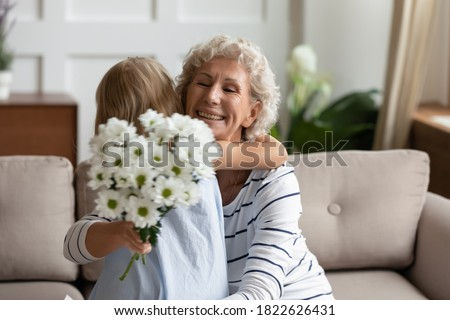 Thank you, my dear! Excited aged grandmother or mature female babysitter feeling grateful and happy embracing with warmth little girl ward or granddaughter giving her flowers congratulating on holiday Сток-фото ©