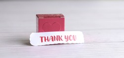 Thank you note in front of a red gift box. A show of appreciation for loved ones.