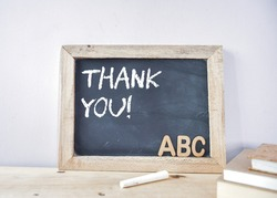 THANK YOU note on chalkboard with 3d wooden alphabet letters at the corner. Teacher's day celebration concept.