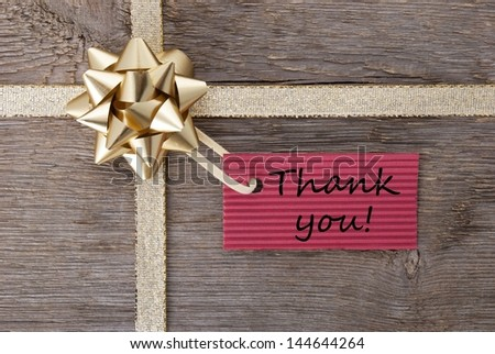 thank you on a red label on a golden gift bow as present background