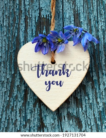 Thank You or thanks greeting card with spring flowers and decorative white heart on a blue wooden background.International Thank You Day or Mother's Day concept. Foto stock ©