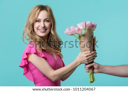 Thank you. Portrait of glad young woman is getting pink spring flowers from man. She is looking at camera and smiling. Isolated