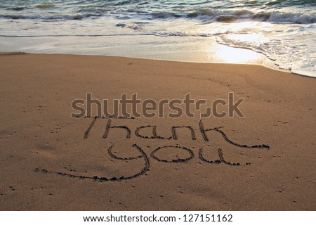 Thank you written in the sand on the beach.