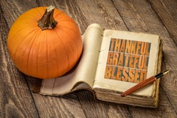 thankful, grateful and blessed inspirational words in vintage letterpress wood type in a retro, leather-bound journal with a pumpkin against rustic wood, Thanksgiving theme