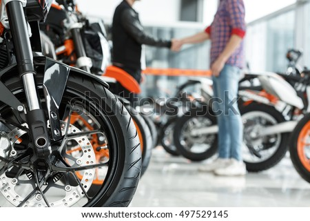 Thanks for help. Selective focus on a motorcycle wheel male customer shaking hands with motorbike salon manager on the background #497529145