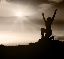 Thanks God and worshipping concept: Silhouette person kneeling over mountain sunset background.