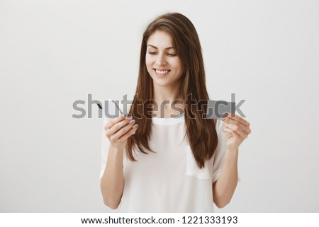 Thanks to her bank she bought new phone. Portrait of pleased and focused attractive woman holding smartphone, smiling, gazing at screen, showing credit card at camera, being satisfied checking account