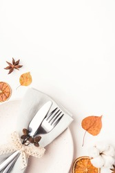 Thanksgiving autumn background. Plate with Cutlery and napkin decorated with autumn leaves, berries and spices. Top view.
