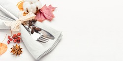 Thanksgiving autumn background. Plate with Cutlery and napkin decorated with autumn leaves, berries and spices. Front view. Close up.