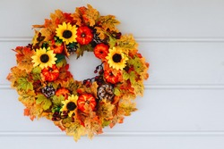 Thanksgiving Autumn wreath with sunflowers, pumpkins and maple leaves on wooden door