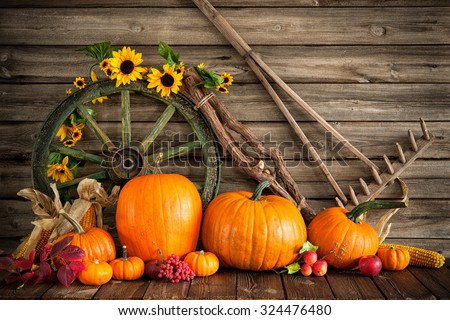 Thanksgiving autumnal still life with pumpkins and old wooden wheel #324476480